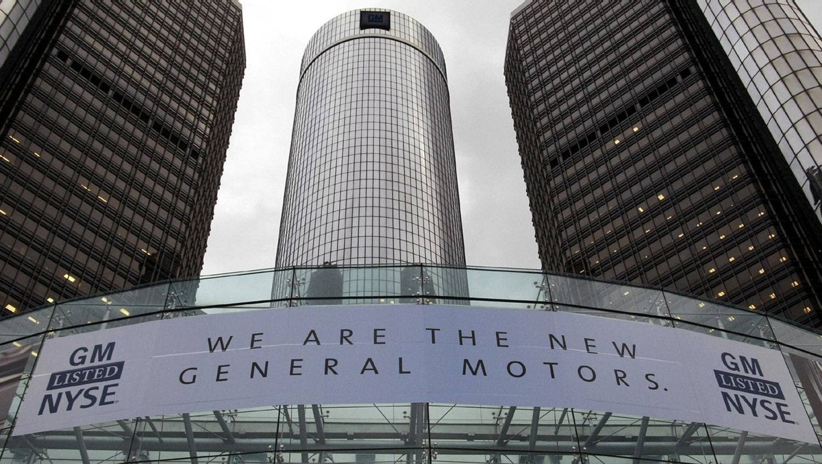 A banner hangs at the front of the General Motors Co world headquarters in Detroit announcing GM's return to the New York Stock Exchange in November, 2010. The auto maker raised $18.1-billion (U.S.) after pricing shares at the top of the proposed range in response to huge investor demand.