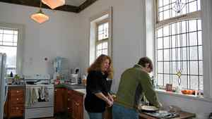 Shannon Kyles, left, and friend Mary Anne Peters work on a pie in the kitchen.