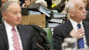 Stacks of cost-estimate documents sit on a desk behind Justice Minister Rob Nicholson and Public Safety Minister Vic Toews as they testify a Commons committee on March 16, 2011.