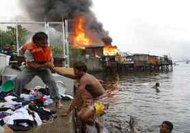 Residents escape with their belongings as fire engulfs houses at a slum community in Manila. At least 1000 houses were razed in the fire.