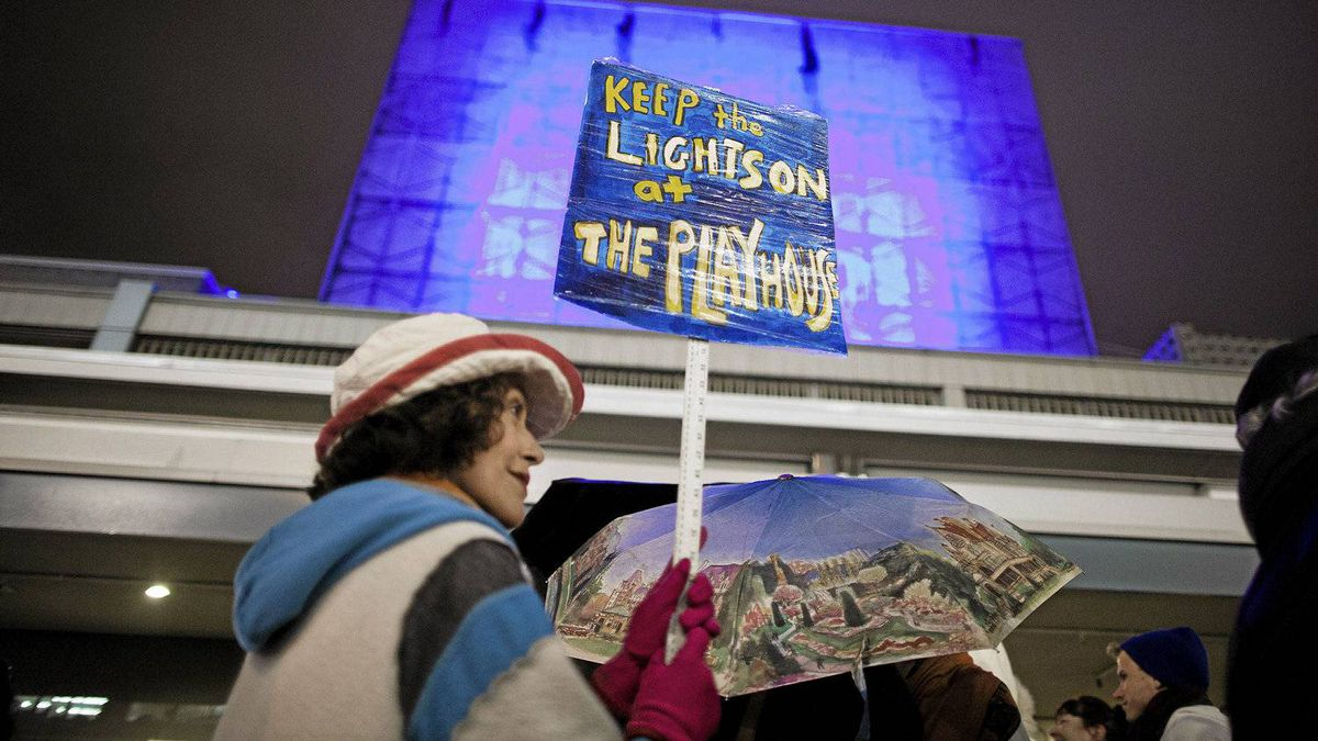 Karin Konoval holds a sign while joined by other supporters, actors and theatre students during a vigil outside the Vancouver Playhouse on the closing night in Vancouver, British Columbia, Saturday, March 10, 2012. After nearly 50 years the Vancouver Playhouse is shutting its doors due to financial troubles.
