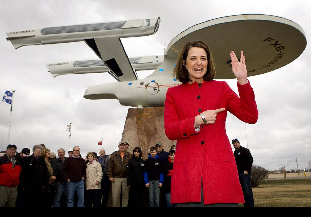 Wildrose leader Danielle Smith shows she can give a Vulcan salute as she stands in front of a model of the Starship Enterprise during a campaign stop in Vulcan, Alberta.