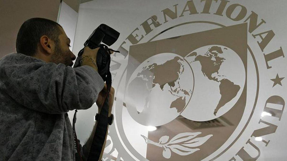 A photographer takes pictures through a glass carrying the International Monetary Fund (IMF) logo during a news conference in Bucharest March 25, 2009.