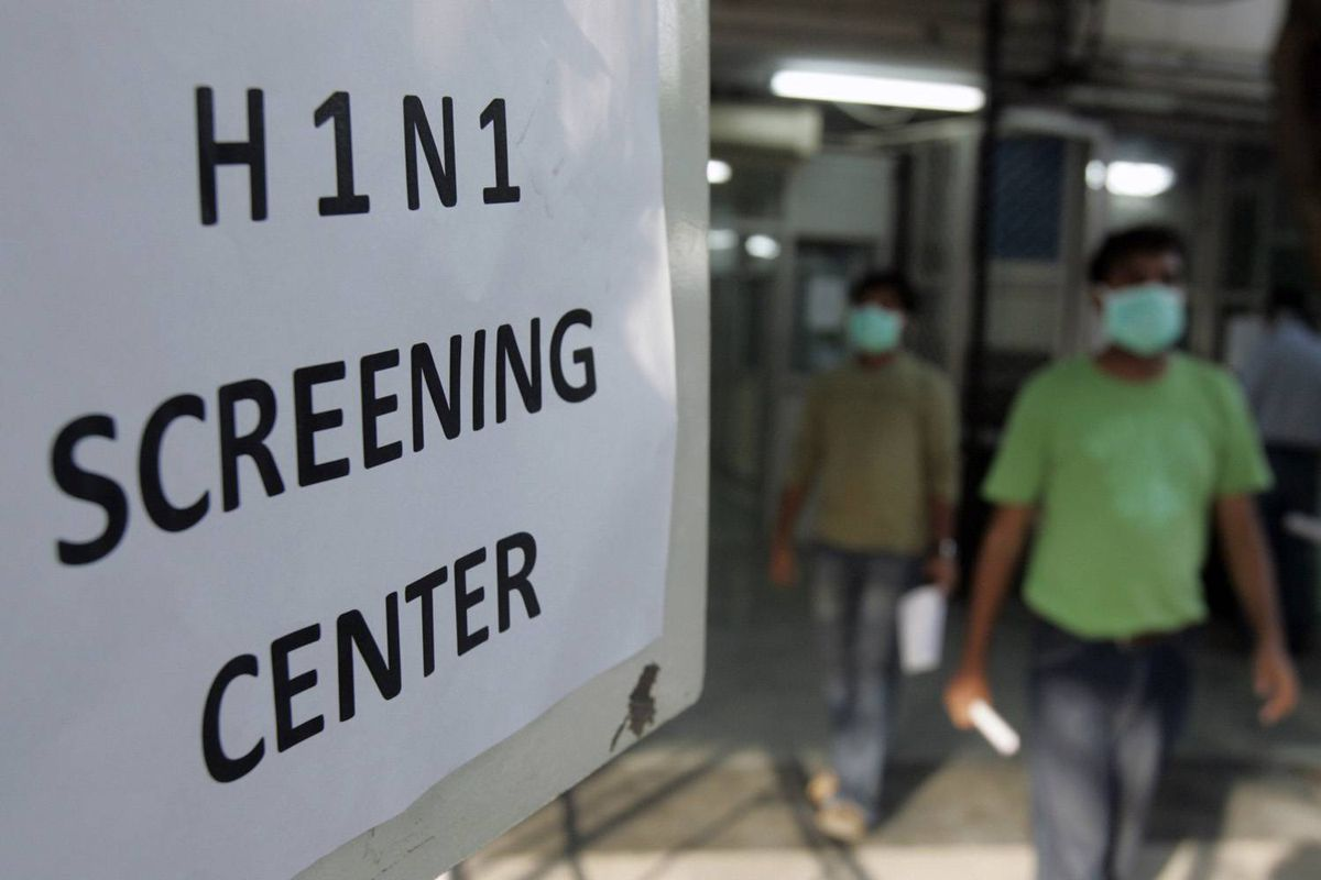 People wearing surgical masks walk out of a H1N1 flu screening centre in Ram Manohar Lohia hospital in New Delhi.
