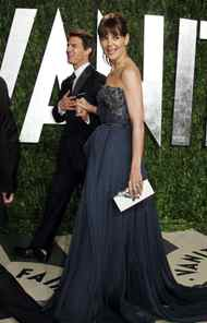 Katie Holmes escorts her tiny, levitating husband into the Vanity Fair Oscar party in West Hollywood on Sunday.
