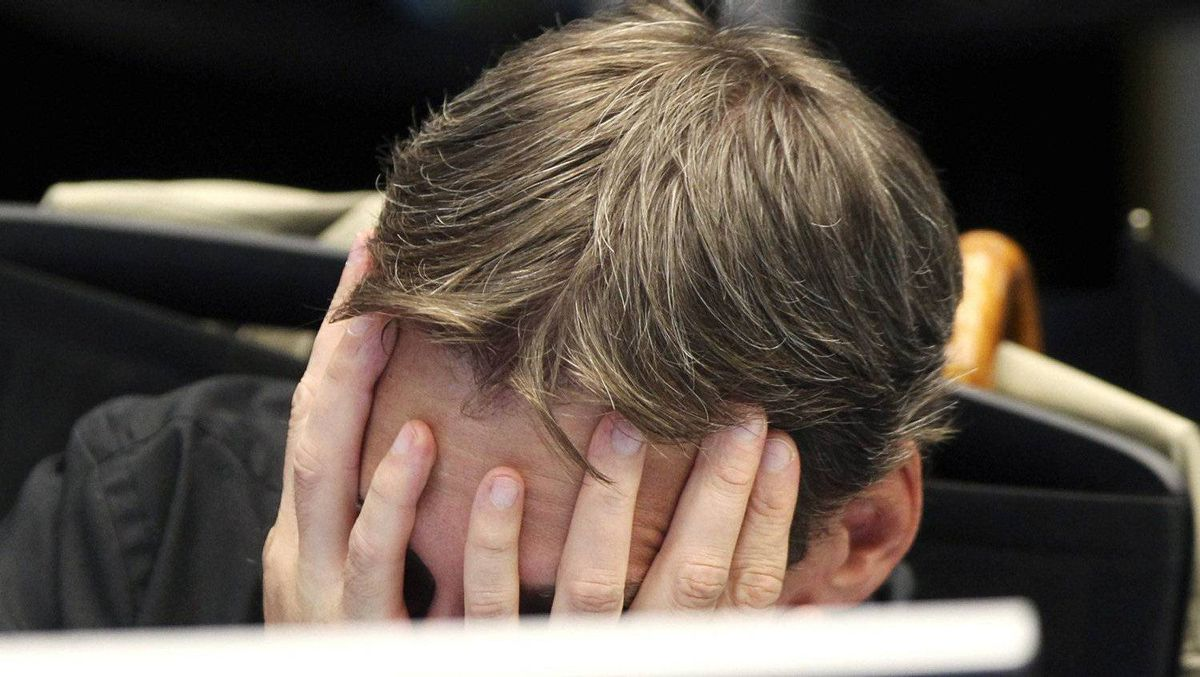 A broker covers his face behind his screen at the stock market in Frankfurt, Germany, Monday, Aug.8, 2011, where the stock index went down after the opening of the stock market.