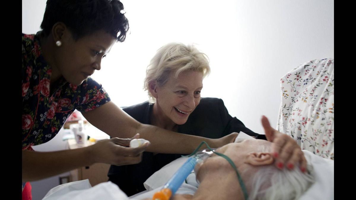 Basia Hoffman sees her mother, Andrée Hoffman, opening her eyes while at Kensington Hospice in Toronto on Feb. 8, 2012. Gisele Mulumba, the staff member at left, helps with some personal care for Mrs. Hoffman.