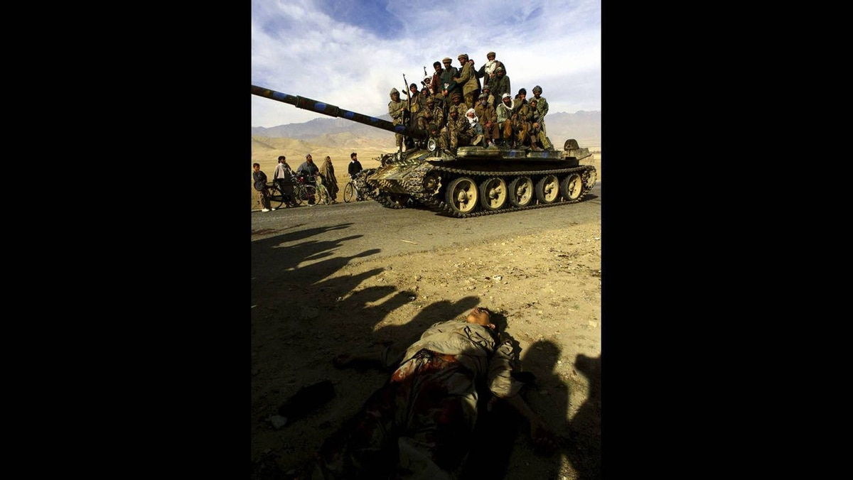 Northern Alliance fighters ride on a T-62 tank past a dead body on the motorway 3 km north of Kabul, in this November 13, 2001.