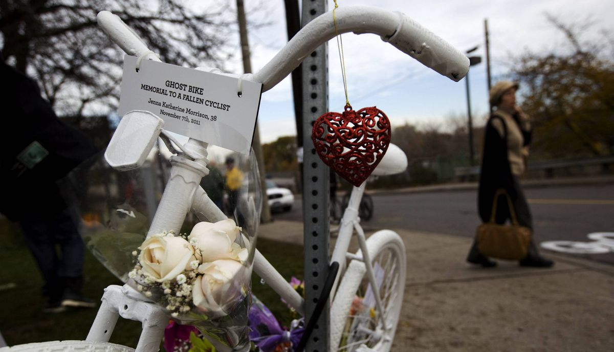 A white 'ghost bike' was secured to a sign at the end of a memorial ride Monday, November 14, for pregnant cyclist Jenna Morrison, who was recently killed after being struck by a truck at Sterling and Dundas in Toronto. The ride culminated at the west-end intersection where candles and flowers have been placed, a stencil drawn and where activists painted bike lane symbols in the place of the 38-year-old mother's death.