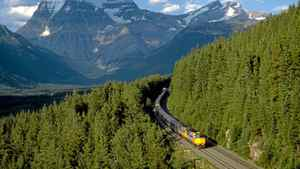 Via Rail's the Canadian making its way through forests overlooked by the Rocky Mountains between Jasper and Vancouver.