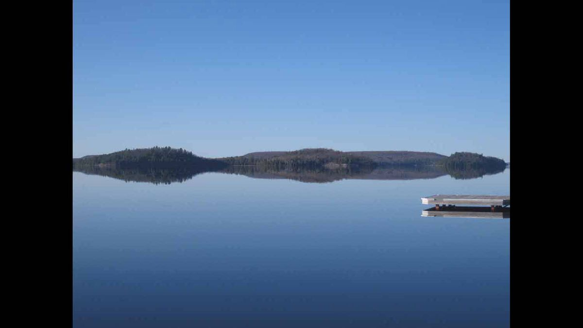 The south shore of Lake of Bays is usually pounded by west and north winds. For a rare moment on Saturday afternoon, the water reflected perfect mirror images of nature and man-made creations.