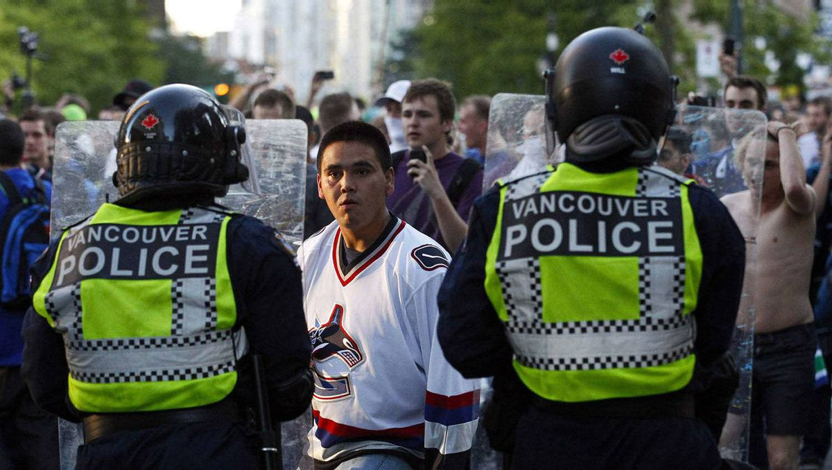 A man confronts Vancouver police during riots after the Canucks lost Game 7 of the Stanley Cup Final to the Boston Bruins.