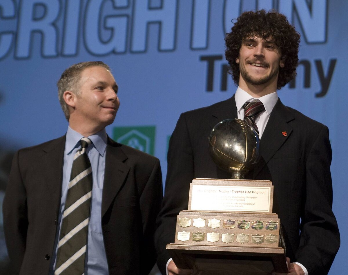 Calgary University Dinos quarterback Erik Glavic holds the Hec Crighton trophy as CIS player of the year for the second time in three seasons while Steve Crighton, grandson of Hec Crighton, left, looks on at awards ceremony Thursday, Nov.26, 2009 in Quebec City. THE CANADIAN PRESS/Jacques Boissinot