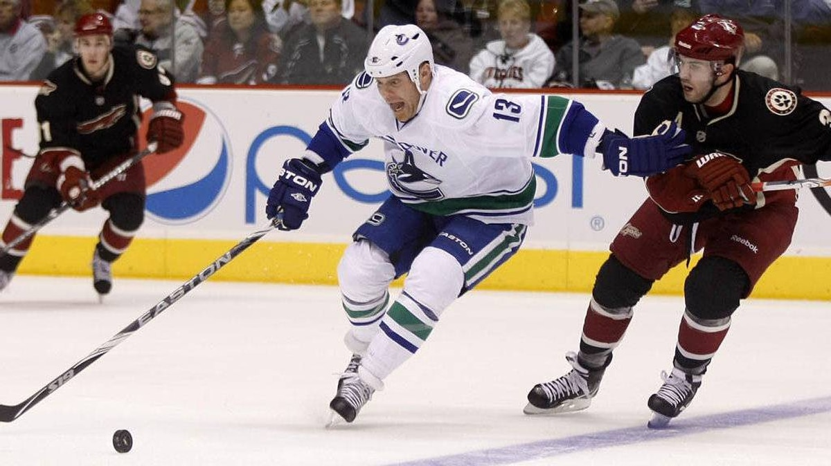 Vancouver Canucks left wing Raffi Torres shields Phoenix Coyotes defenseman Keith Yandle from the puck in the third period during an NHL game in Glendale, Arizona, March 8, 2011.