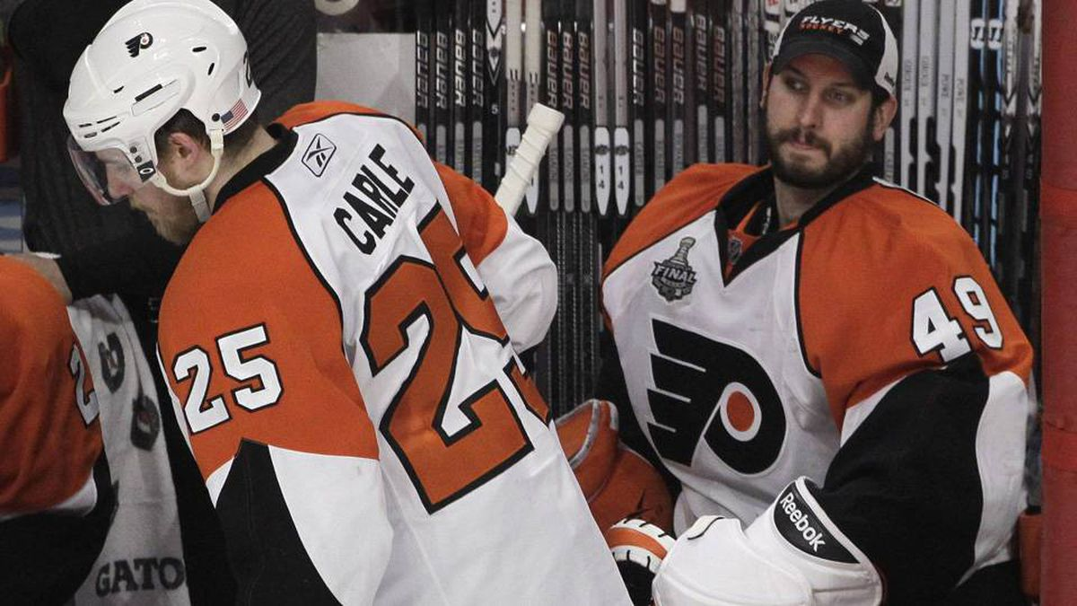 Philadelphia Flyers goalie Michael Leighton (49) sits on the bench as Flyers defenseman Matt Carle (25) comes off after a shift against the Chicago Blackhawks in the second period of Game 5 of the NHL Stanley Cup hockey finals on Sunday, June 6, 2010, in Chicago. Leighton was pulled for goalie Brian Boucher. (AP Photo/Charles Rex Arbogast)