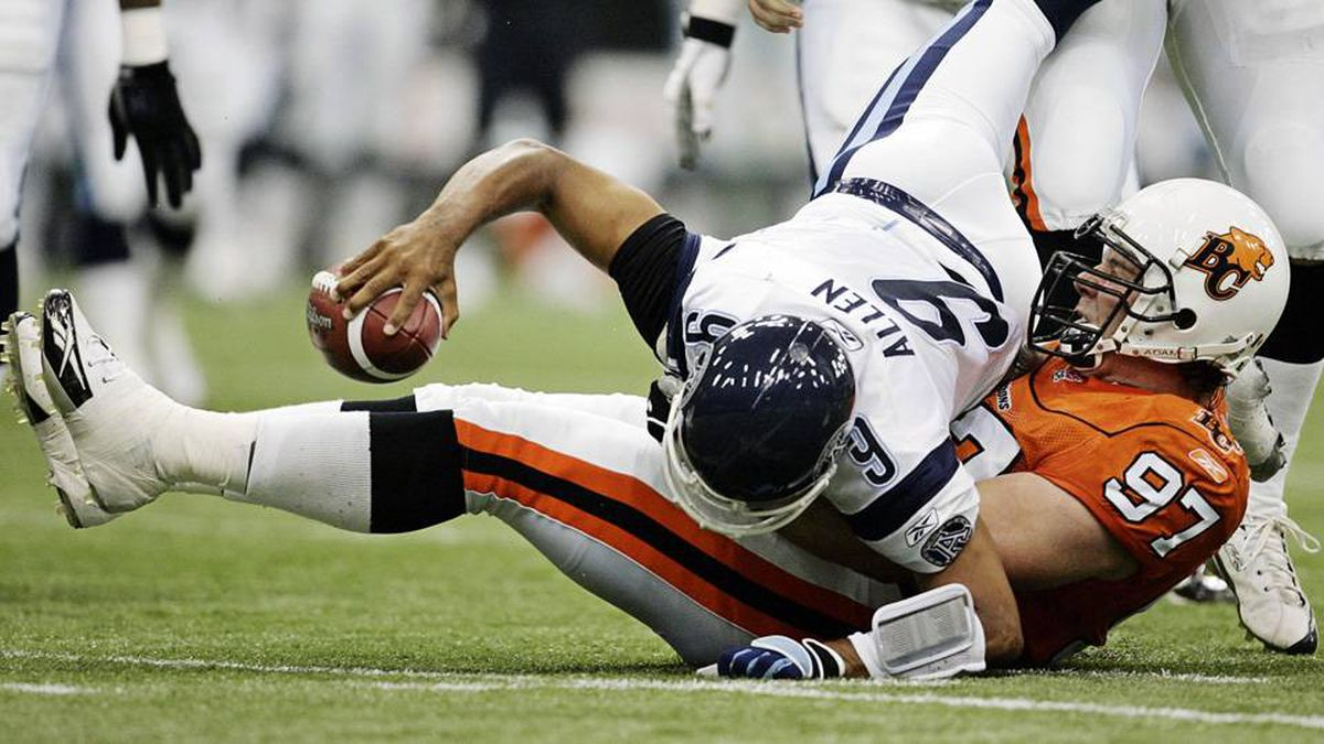 Toronto Argonauts quarterback Damon Allen (9) is sacked by BC Lions defensive end Brent Johnson (97) during the first half of Canadian Football League play in Vancouver, British Columbia July 15, 2005.