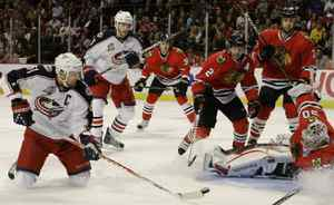 Columbus Blue Jackets left wing Rick Nash, left, takes a shot on goal from his knees at Chicago Blackhawks goalie Corey Crawford, right, during the first period of their NHL hockey game Saturday, Oct. 23, 2010 in Chicago.