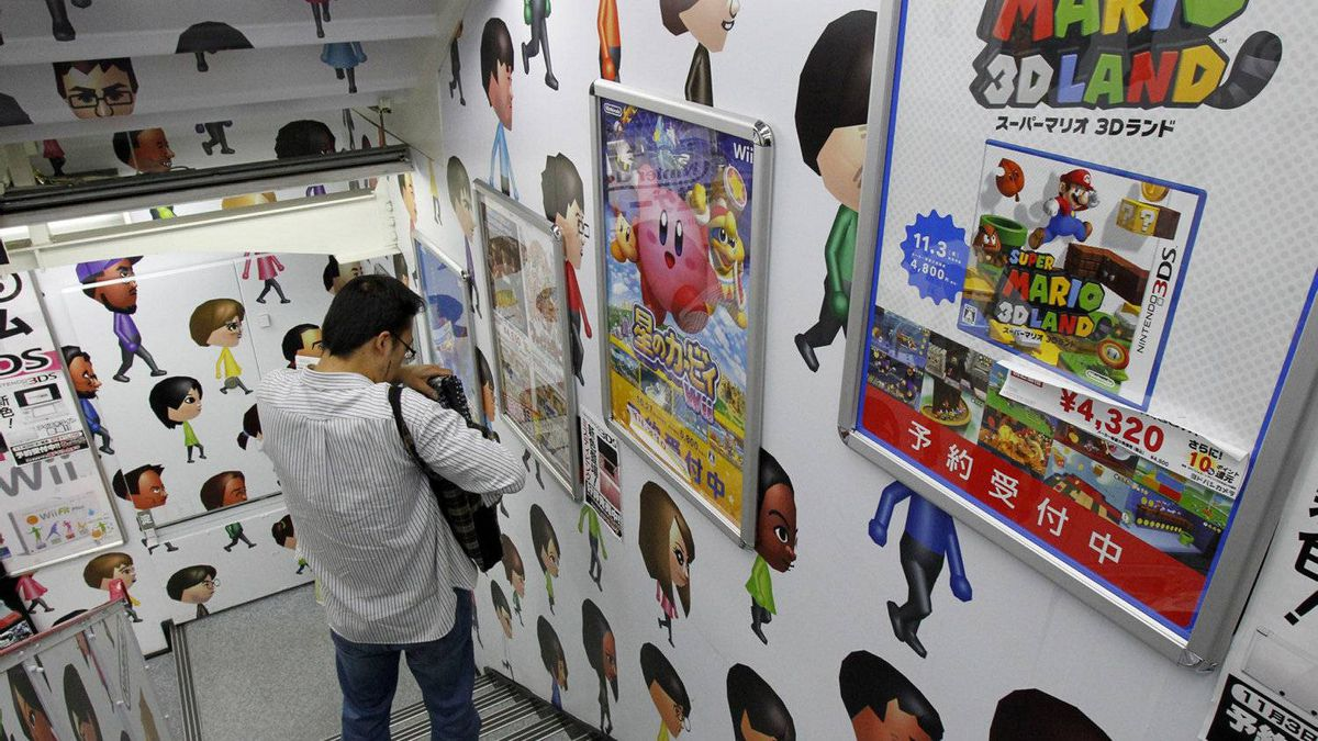 A man walks down the stairs covered with Nintendo Wii characters at an electronics retailer in Tokyo, Thursday, Oct. 27, 2011.