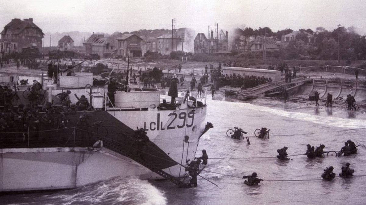 Canadian troops wade ashore after landing in the D-Day invasion at Bernieres-sur-Mer in this June 6, 1944 handout photo. Hundreds of veterans are gathering on June 2009 in Normandy to commemorate the 65th anniversary of the D-Day invasion. The building now known as Queen's Own Rifles House is at left.