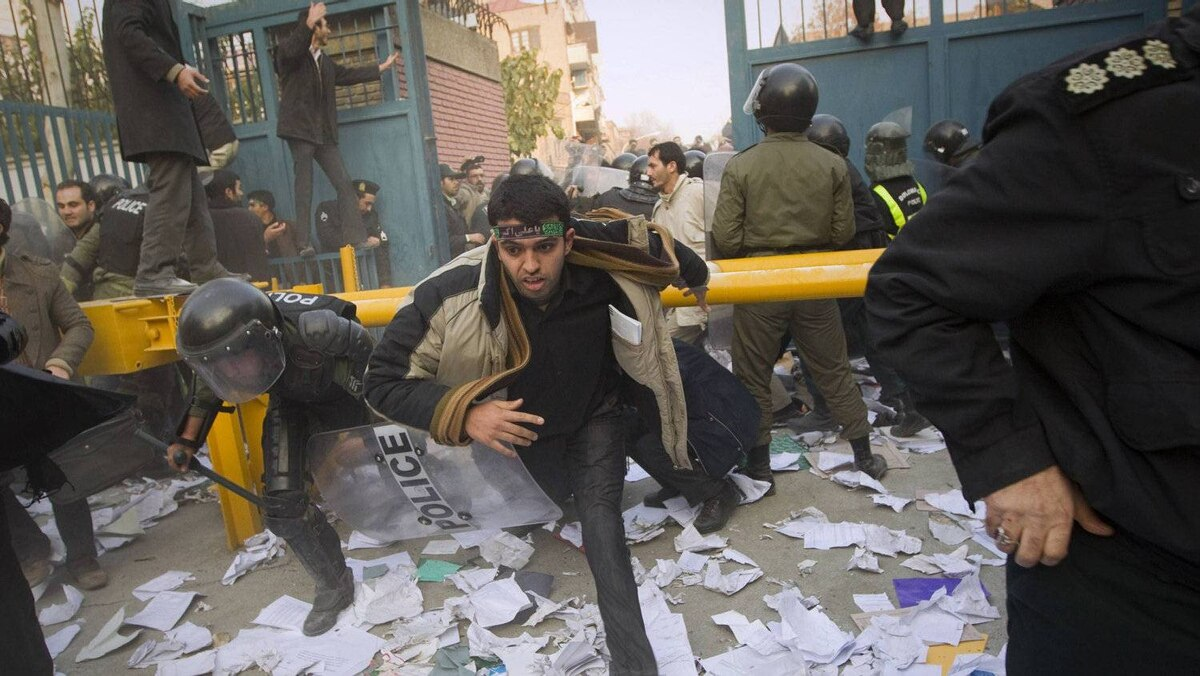 Police chase protesters as they enter the gate of the British embassy in Tehran November 29, 2011.