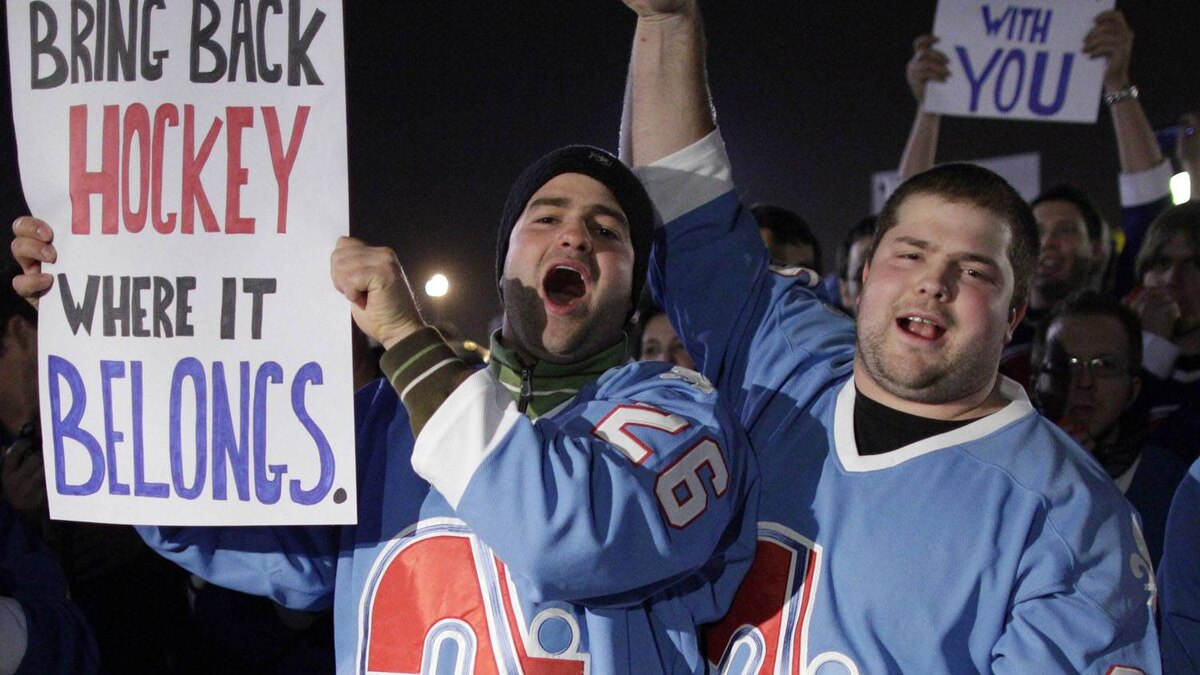 Fans of the Quebec Nordiques hold signs outside the location where an NHL hockey game between the New York Islanders and the Atlanta Thrashers is being held in Uniondale December 11, 2010. The fans had gathered to show that their city Quebec should have an NHL team of their own. The Quebec Nordiques last played in the NHL 15 years ago. REUTERS/Chip East