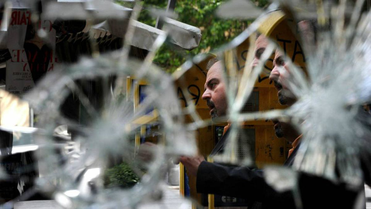 A Greek man is reflected in a broken mirror as he checks newspapers in the center of Athens