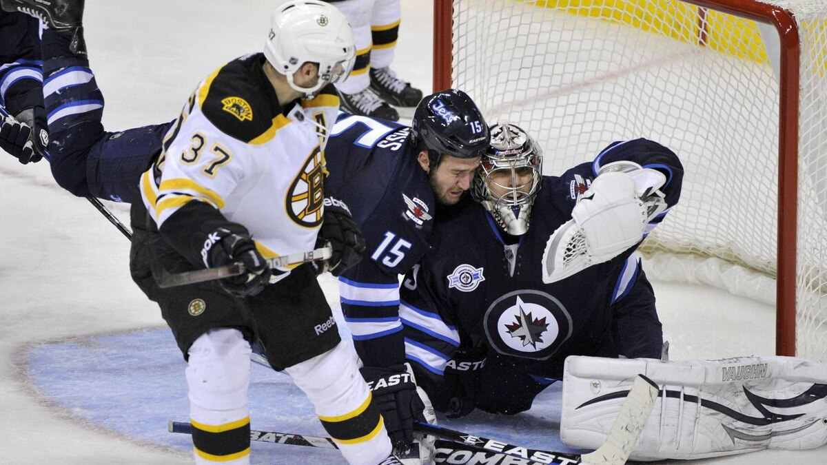 Winnipeg Jets goaltender Ondrej Pavelec makes a save on Boston Bruins' Patrice Bergeron (37) as Tanner Glass (15) falls during the third period of their NHL hockey game in Winnipeg February 17, 2012. The Jets won 4-2. REUTERS/Fred Greenslade