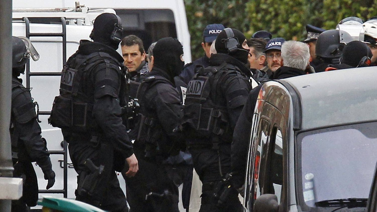 French special intervention police officers are seen near the building where the chief suspect in a killing spree was holed up in Toulouse, on March 22, 2012.