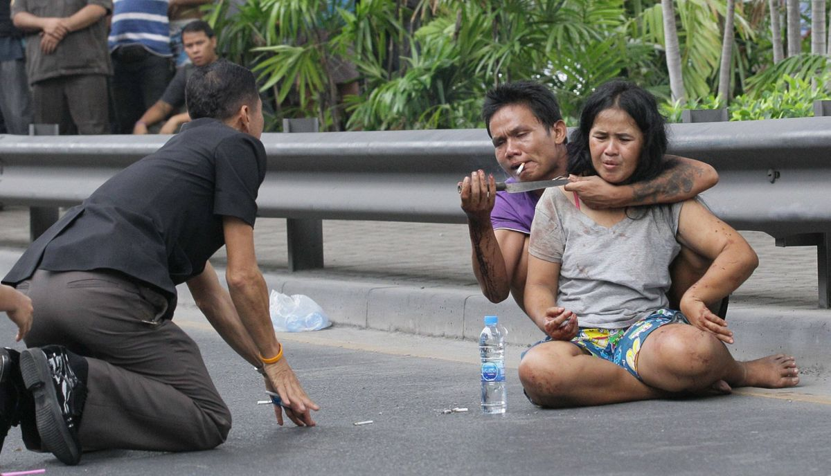 A Thai policeman talks to Sakdawut Hamsiri, 30, who holds a knife against his wife Thawee Naiyanit on a street in Bangkok, Thailand Thursday, April 5, 2012. The 6-hour knifepoint hostage ended when the police used a Taser gun to electroshock him and took him to the police station. Police said the man was under the influence of drugs.