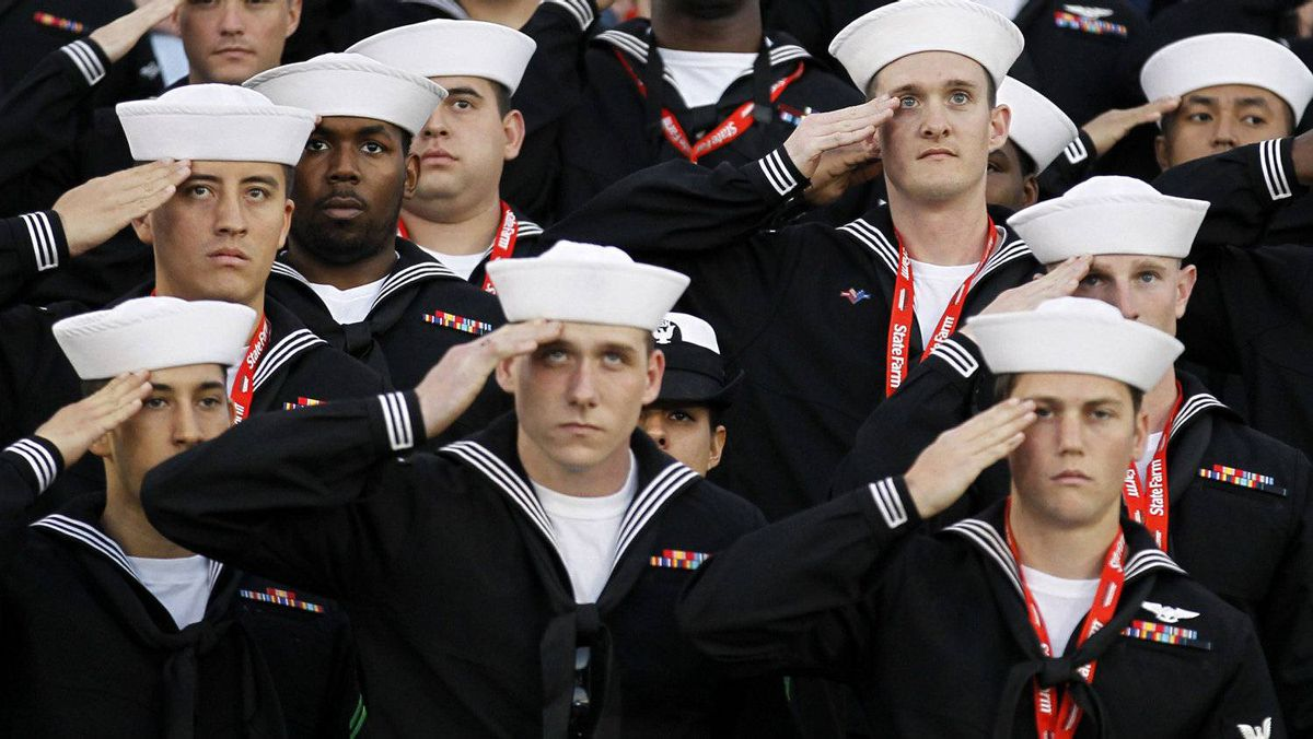 U.S. sailors salute during the retiring of the colors onboard the USS Carl Vinson during the NCAA Carrier Classic men's college basketball game between Michigan State Spartans and North Carolina Tar Heels in Coronado, California November 11, 2011. REUTERS/Mike Blake