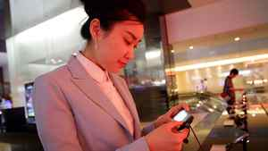A staff member inspects a cellphone at Samsung's main showroom in Seoul.