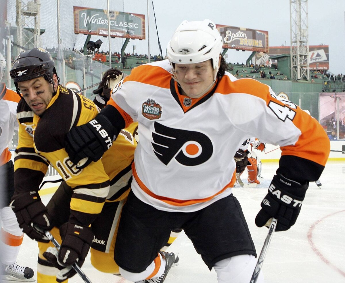 Boston Bruins left wing Marco Sturm (16) and Philadelphia Flyers right wing Arron Asham (45) fight for a puck in the corner during the third period of the New Year's Day Winter Classic NHL hockey game on an outdoor rink at Fenway Park in Boston, Friday, Jan. 1, 2010. (AP Photo/Elise Amendola)