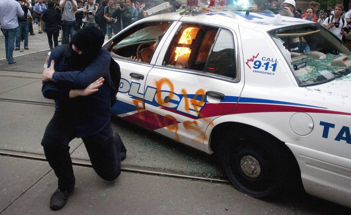 An anti G20 protester poses for a photo in front of a burning police car that was set on fire during violent protesting in downtown Toronto.