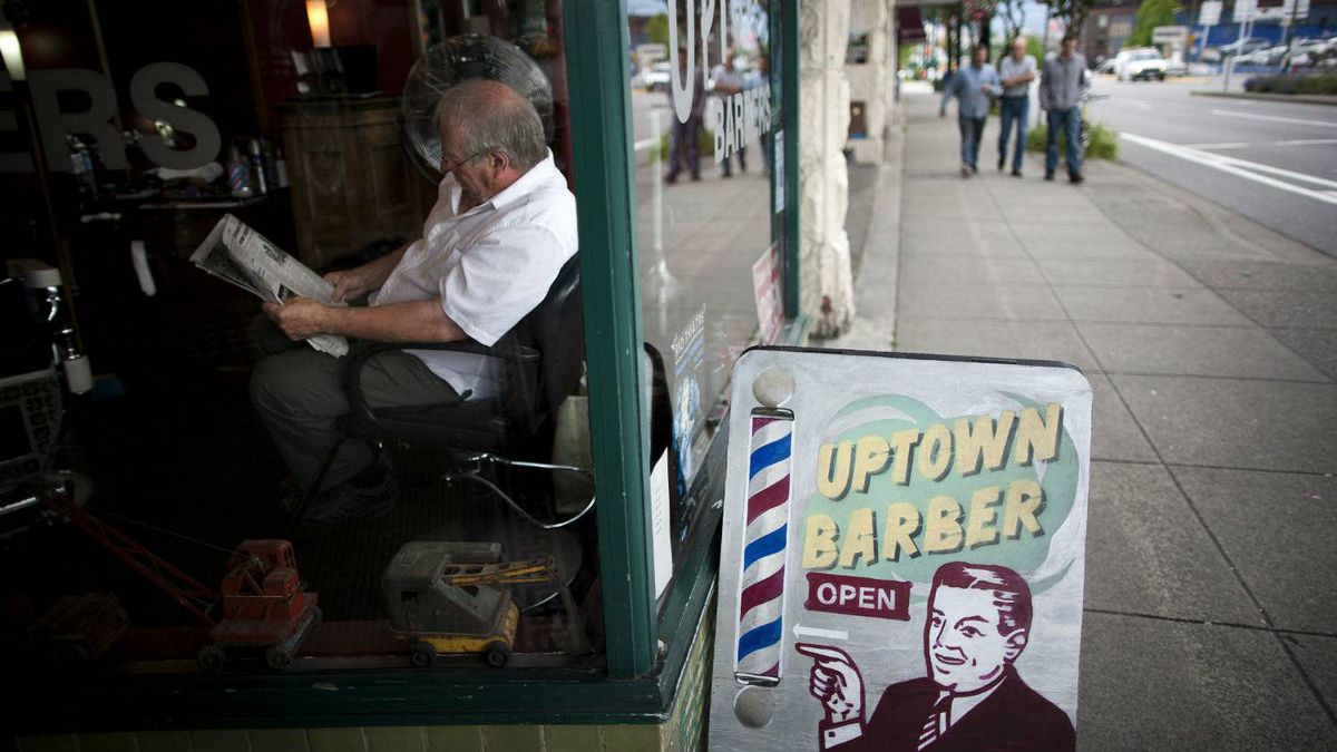 A barber waits for customers while reading the newspaper at the Uptown Barber shop in the Mount Pleasant neighbourhood of Vancouver, British Columbia, June 30, 2011.