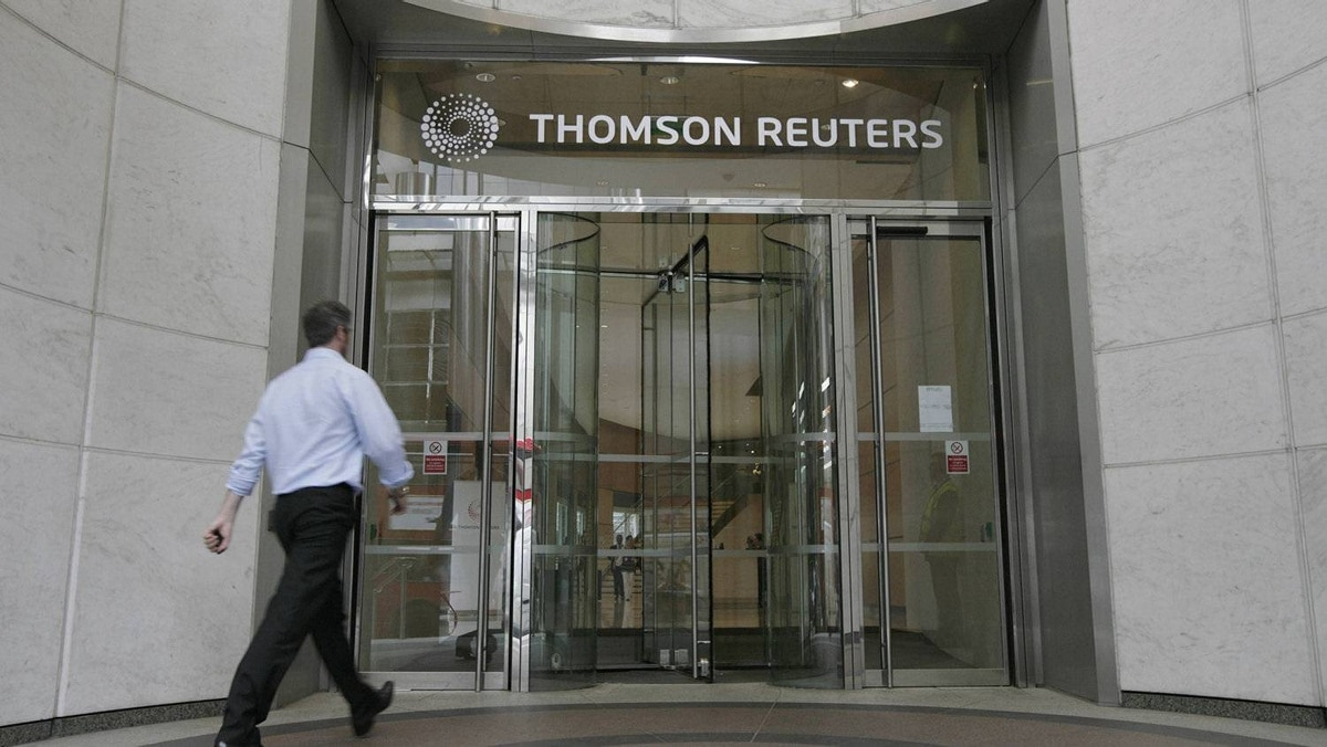 A worker enters the Thomson Reuters building in the Canary Wharf financial district of London on Aug. 6, 2009.