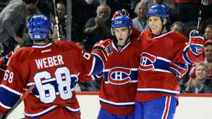 Louis Leblanc #71 of the Montreal Canadiens (centre) celebrates his first career NHL goal with team mates Michael Blunden #45 and Yannick Weber #68 during the NHL game against the Philadelphia Flyers at the Bell Centre on December 15, 2011 in Montreal, Quebec, Canada. The Canadiens defeated the Islanders 5-3.