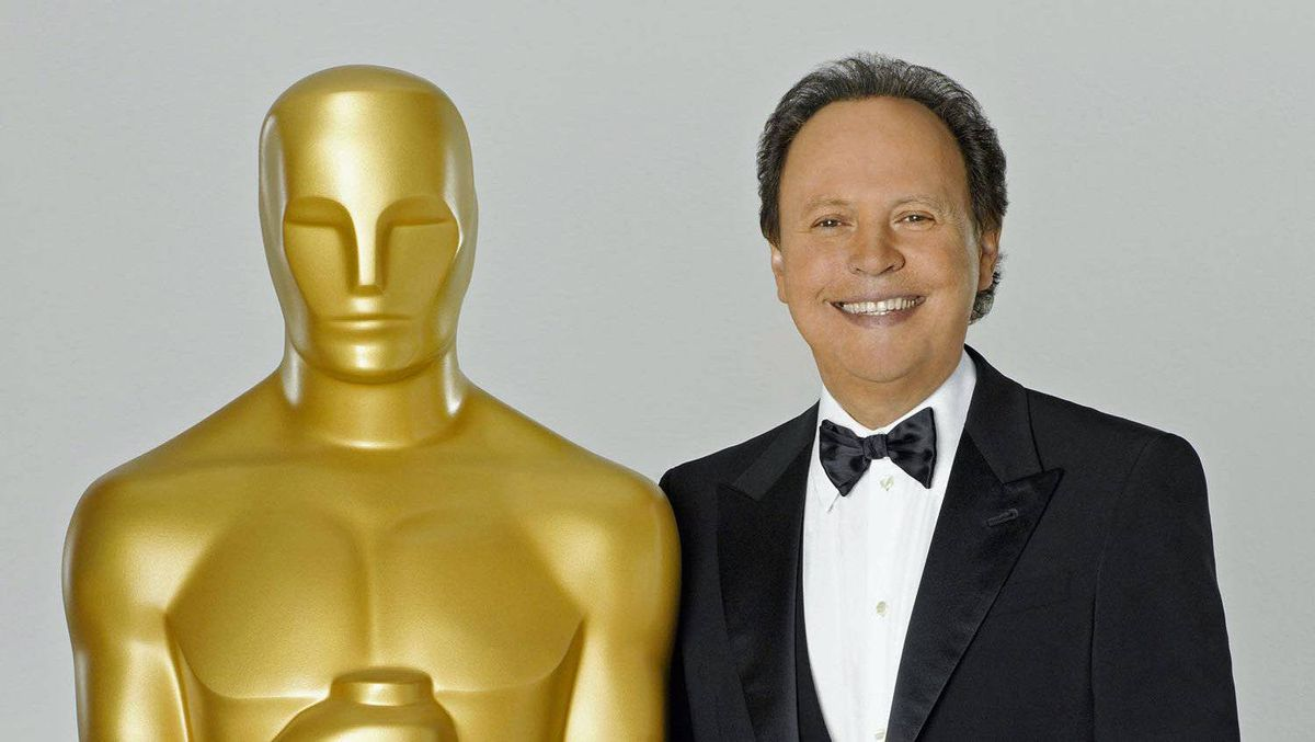 Billy Crystal, host for the 84th Academy Awards, poses in this undated publicity photograph with a large Oscar statuette.