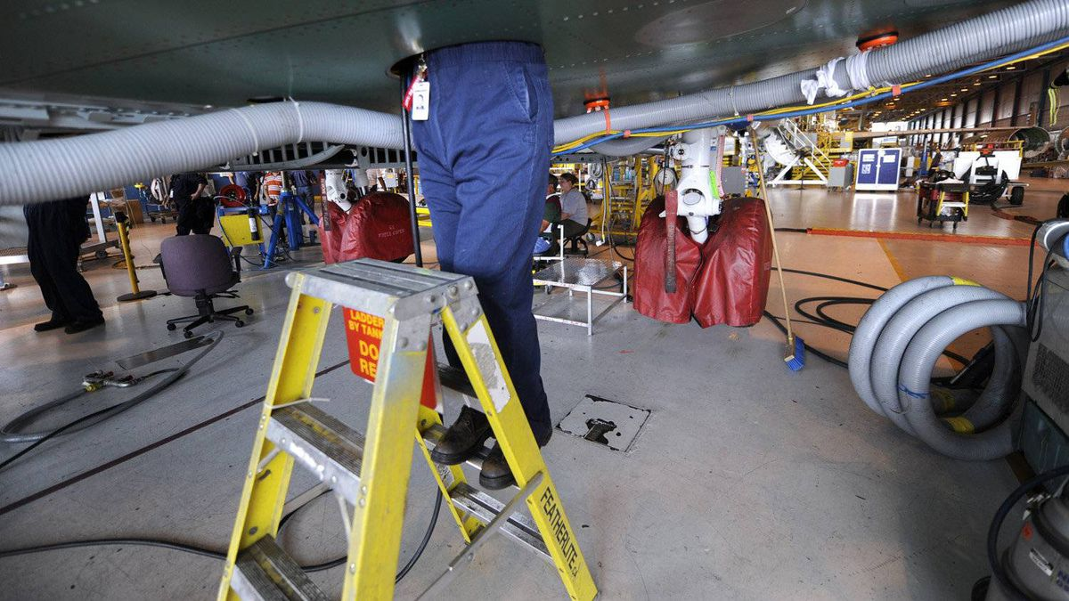 An employee works on the undercarriage of a Global Express jet.