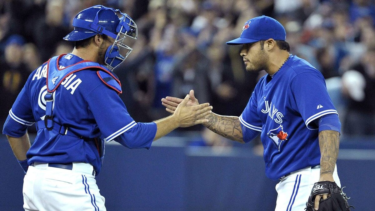 Toronto Blue Jays catcher J.P. Arencibia and pitcher Sergio Santos (R) celebrate their win against the Boston Red Sox during the ninth inning of their MLB American League baseball game in Toronto April 11, 2012.