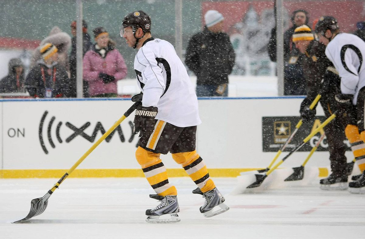 Mark Recchi #28 of the Boston Bruins helps clear some of the snow before practice for the Bridgestone NHL Winter Classic on December 31, 2009 at Fenway Park in Boston, Massachusetts. (Photo by Elsa/Getty Images)