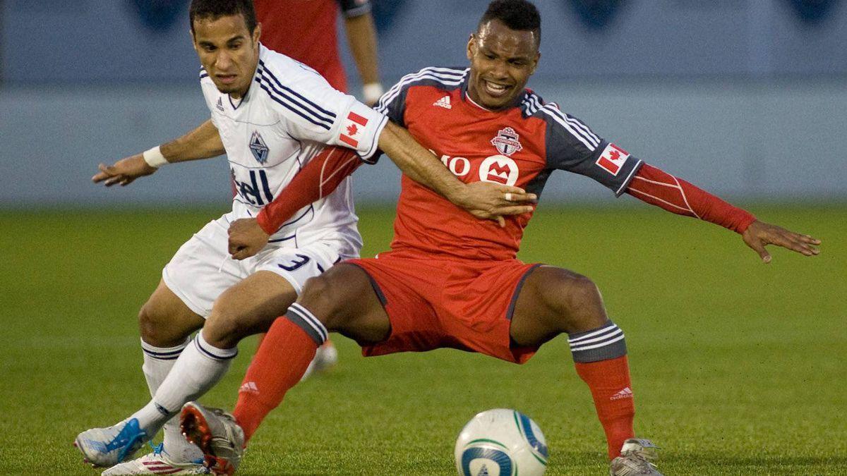 Vancouver Whitecaps' Camilo da Silva Sanvezzo, left, takes down Toronto FC's Julian de Guzman in Vancouver, May 18, 2011.