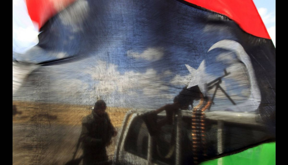 A rebel fighter seen behind a Kingdom of Libya flag near the front line along the western entrance gate of Ajdabiyah on April 18, 2011.
