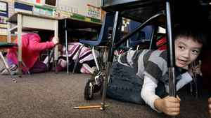 Joseph Kim takes cover under his desk during an earthquake drill at Hollyburn Elementary School in West Vancouver, B.C., on Wednesday January 26, 2011.