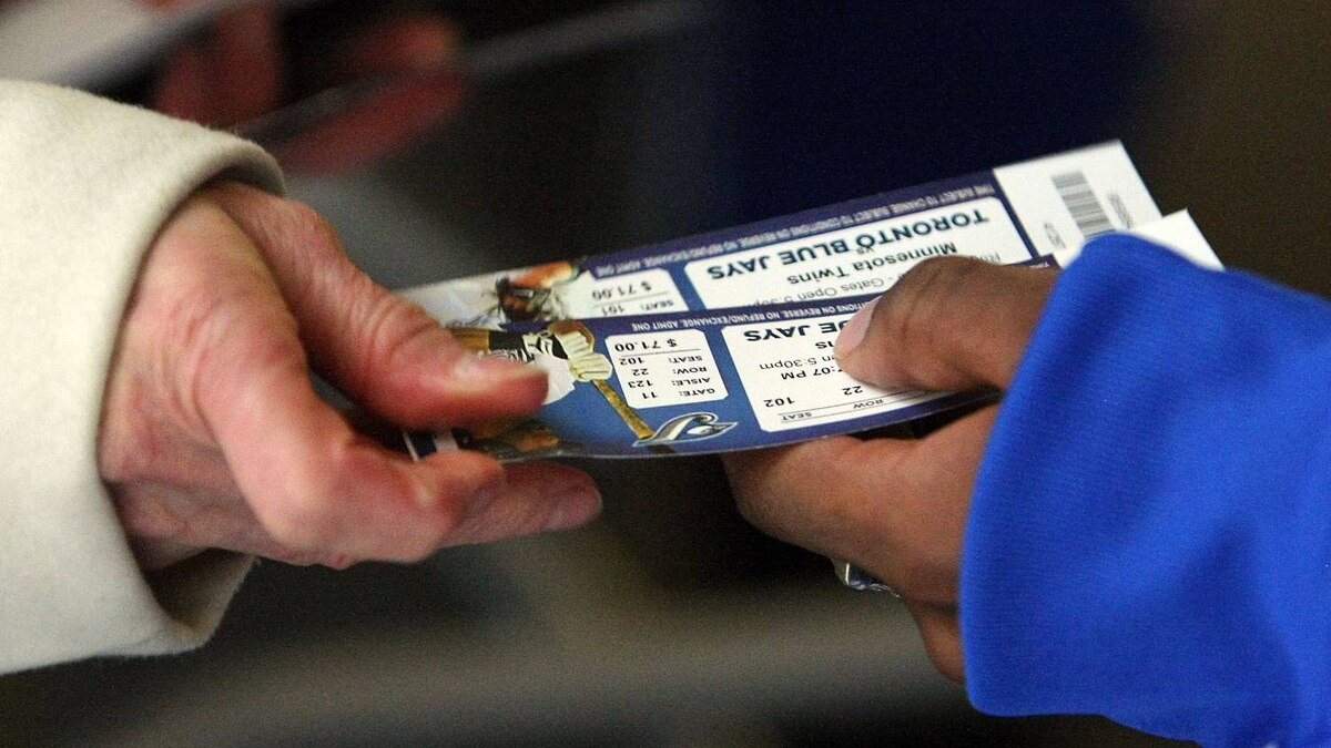 A fan comes through the turnstile and hands tickets to a gate attendant prior to the home opener for the Toronto Blue Jays as they face the Minnesota Twins during their MLB game at the Rogers Centre April 1, 2011 in Toronto, Ontario, Canada.(Photo By Dave Sandford/Getty Images)