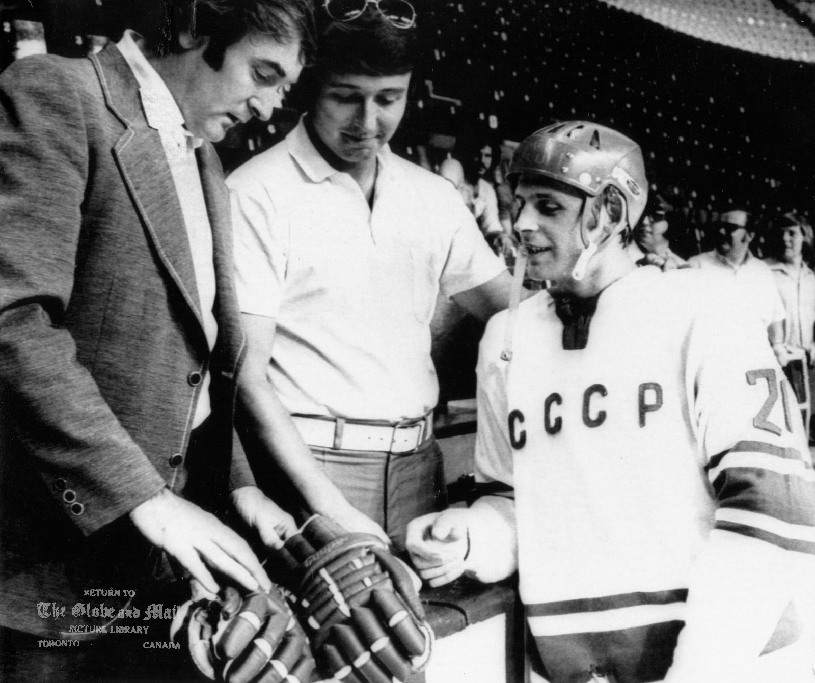 SEPTEMBER 1, 1972 -- MONTREAL -- FRIENDLY CONVERSATION -- Team Canada goalie, Eddie Johnston, left, and defenceman Brad Park, centre, have a friendly conversation with Russian forward Vyacheslav Solodukhin of the USSR national hockey team at the St. Lawrence Arena in suburban Montreal, September 1, 1972. Team Canada will meet the Russians in the first game of the Canada-Russia Summit Series on Sept. 2, 1972. CP PHOTO