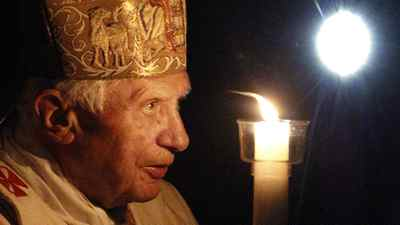 Pope Benedict XVI holds a tall, lit candle as he enters the darkened St. Peter's Basilica in the Vatican on Saturday.