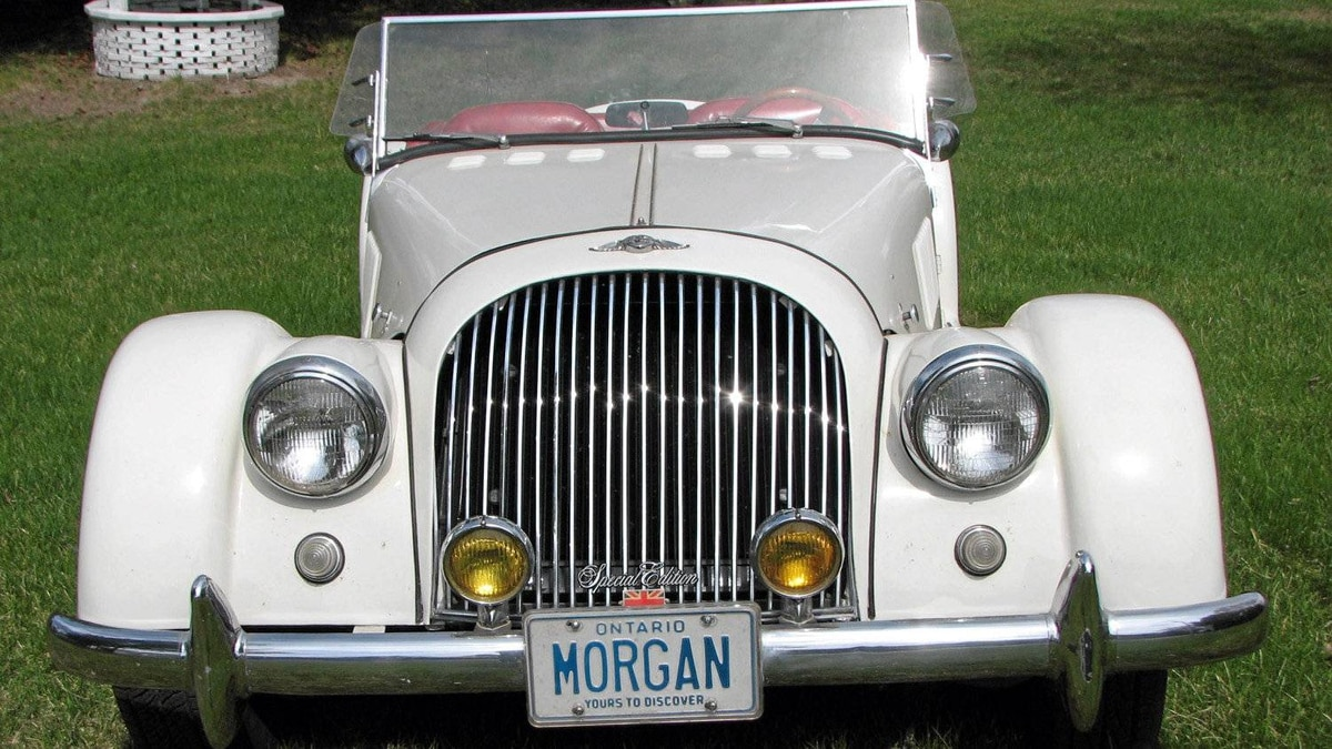 """The flaring front fenders and fared-in headlamps framing a vertically slatted grille immediately provide the appropriate visual clues, and the personalized licence plate """"MORGAN"""" should have removed any doubt as to what it was. But wait a sec, isn't that grille about half-again as wide as it should be, along with the hood behind it?"""