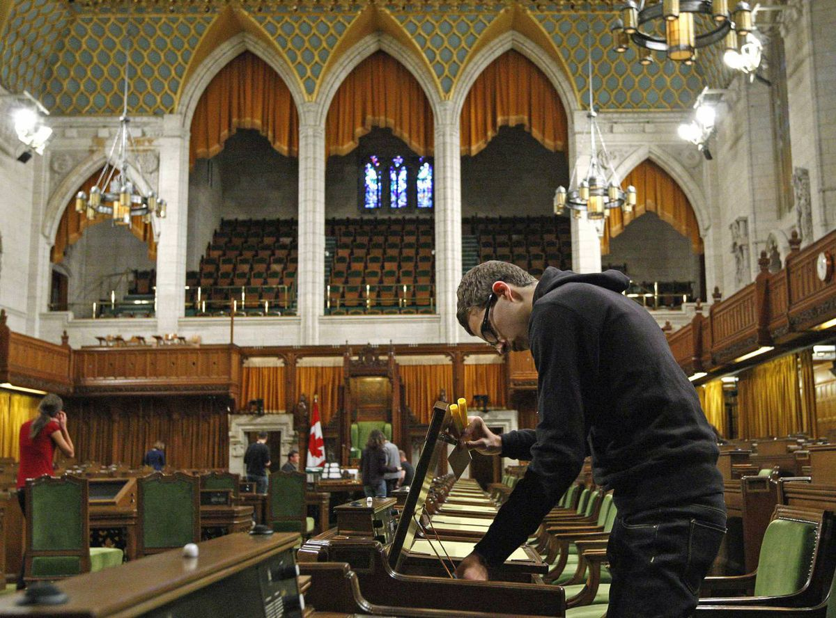 A page arranges a desk in the House of Commons on Thursday, Sept. 10, 2009, in preparation for the return of Parliament the following week.