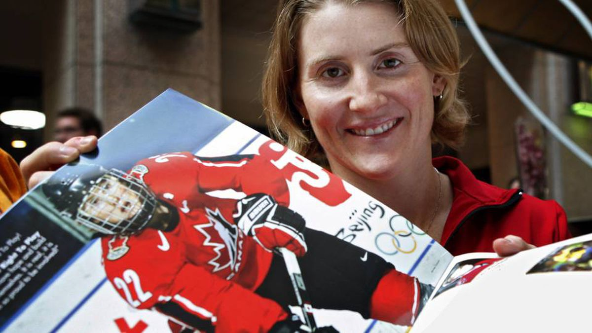 Canadian Olympic women's hockey player Hayley Wickenheiser holds her page open at the launch of an Olympic calendar fundraising project in Calgary, Thursday, Sept. 10, 2009. Proceeds from the calendars support Right To Play sports programs across Africa, Asia, and South America.
