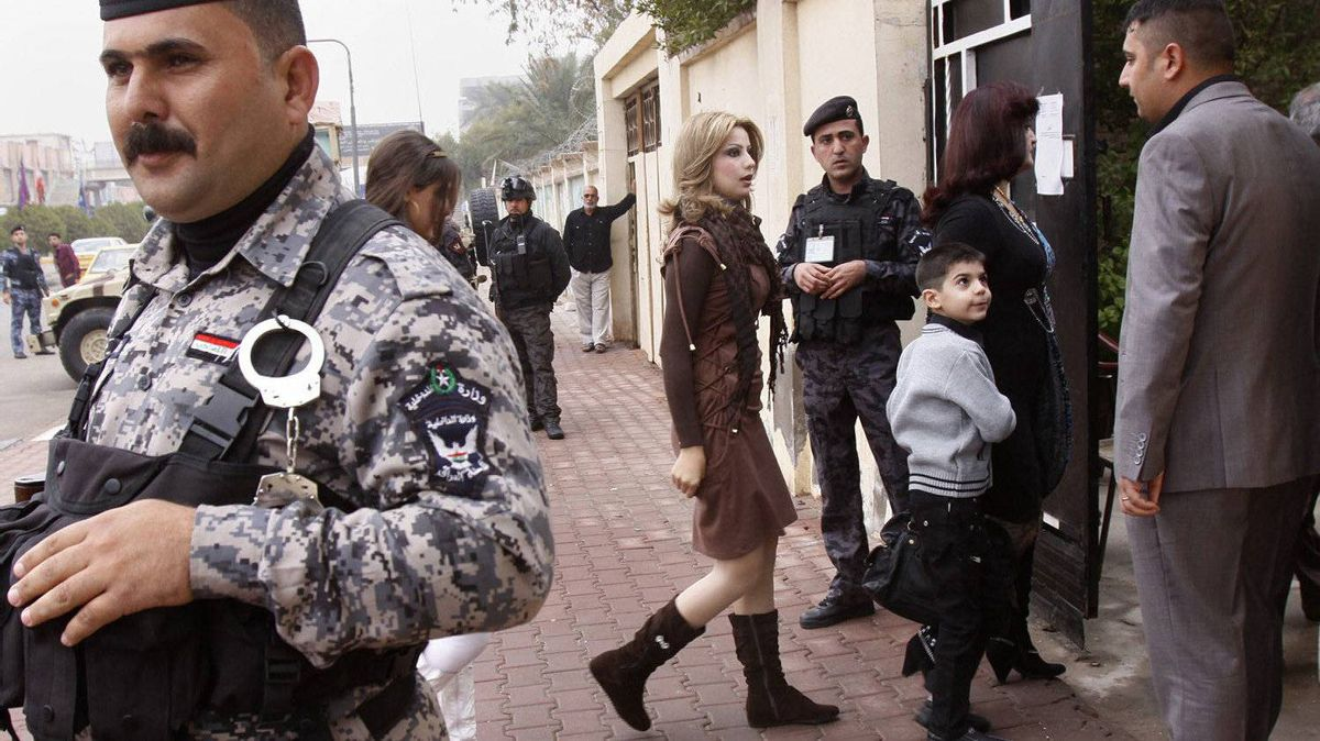 Iraqi security forces stand guard as worshippers entering a church in Basra, Iraq's second-largest city, 340 miles (550 kilometers) southeast of Baghdad, Iraq, Sunday, Dec. 25, 2011.